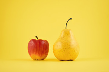 Pear and apple decoration stock images. Yellow pear and red apple on a yellow background. Fruit home decor. Plastic decorative fruit