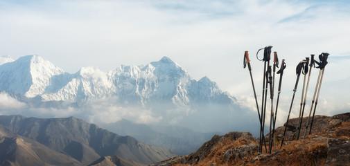 Trekking sticks on background mountains range. Panoramic view. Wall mural