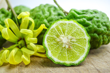 Bergamot fresh fruit on wooden background with yellow flower : natural herb food, spa, hair and body