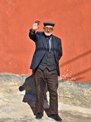 Elderly old Turkish rural man is waving and says hi who lives in a small town in Turkey.