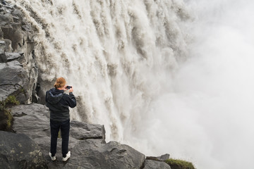 Man in black taking picture of waterfall on cliff edge in Vatnayokull national park, Dettifoss waterfall, Iceland