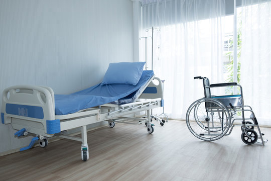 Wheelchair and patient bed in the room of hospital