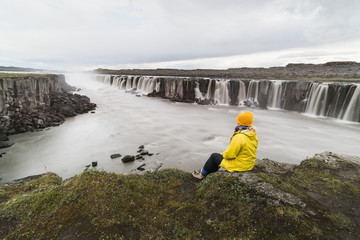Woman sitting on the cliff edge next to Selfoss waterfall in Vatnayokull national park, Iceland