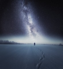 Starry night sky and man silhouette standing on snow