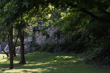 A pretty rock building in the shadows nestled amongst the trees makes a pretty scenery.