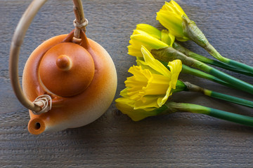 One brown teapot with several yellow narcissus on the wooden background