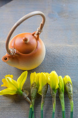 One little brown teapot with several yellow narcissus on the wooden background