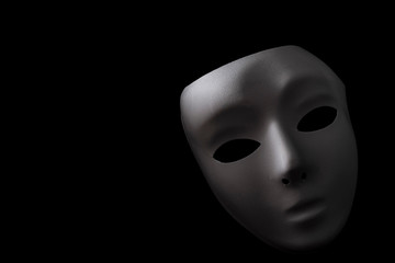 Shadowy disguise, secret society and creepy emotionless figure concept with a vintage white blank mask with dramatic light and dark shadow isolated on black background with copy space