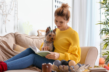 Woman with cute dog reading book at home