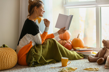 Woman reading book at home on autumn day Wall mural