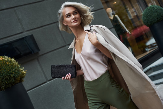 Fashion. Young stylish woman walking on the city street looking aside smiling happy close-up