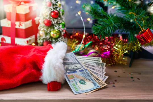 Dollar banknotes in Santa sock and Christmas decoration background