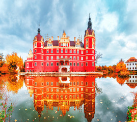 Fototapeta Bad Muskau Park and Palace - Famous UNESCO World Heritage site in Germany and Poland. Amazing Seasonal Autumn landscape with reflections of Great Classic architecture in Pond waters. Yellow leaves.