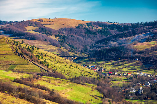 village in a valley. november weather. grassy rural fields on hills above settlement. lovely sunny day.