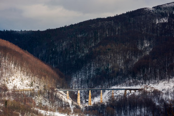winter rail road transportation in mountains. old viaduct between the hills