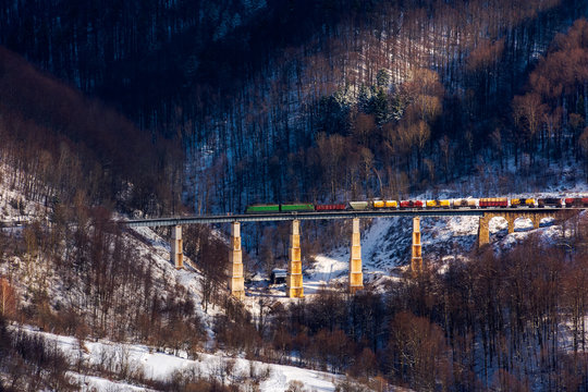 winter rail road transportation in mountains. freight train with colorful carriage on the old viaduct