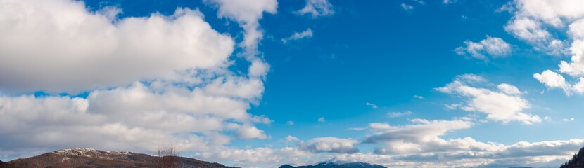 panorama of wonderful winter sky with fluffy clouds above the ridge. beautiful nature background, useful for compositing