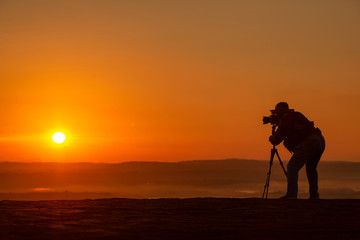 Silhouette of photographer on top of mountain at sunset background