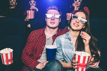 Two young people are sitting close to each other. They have special glasses on their faces to watch movie. Girl is holding basket with popcorn and one piece of it in her hands. Man has a cup of coke.