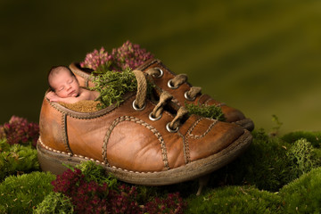 Newborn baby sleeping in old brown shoes