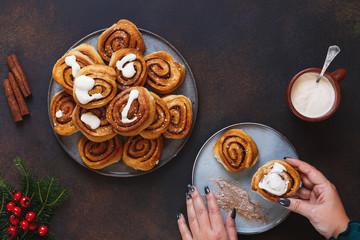 Cinnamon sugar cardamom rolls. A hand holding a cinnamon bun over plate. Top view, rustic festive table
