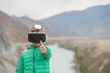 Little boy in virtual reality glasses showing thumbs up on the background of the mountains. Empty space for text