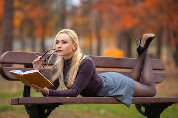 Student girl reading book in the autumn park.