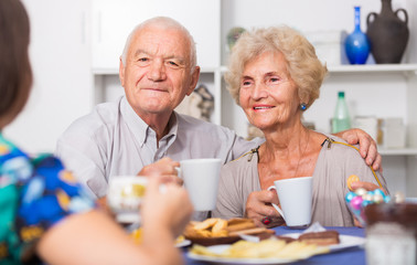Smiling elderly spouses enjoying tea with girl