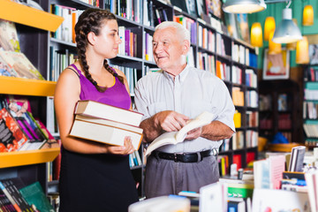 Old man with granddaughter are reading books