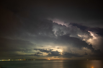 Thunderstorm over the sea, lightning beats the water