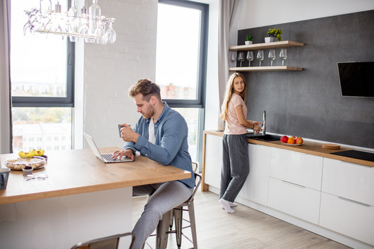 gorgeous woman cleaning the kitchen while her husband surfing the net. wi-fi, technology concept. working at the weekend.