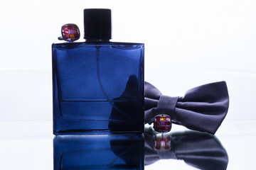 a bottle of perfume and a butterfly tie and cufflinks. concept of a man's gift
