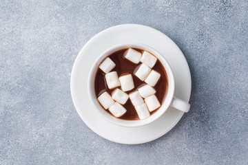 Cup of hot chocolate with marshmallow in the center of the gray table