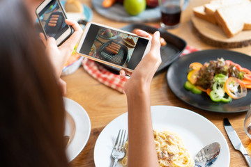 Close up hands of woman taking photo of dinner food on the table