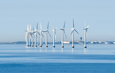Offshore wind turbines on the coast of Copenhagen in Denmark with the airport in the background