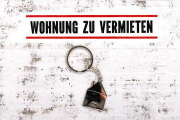 """Nachricht """"Wohnung zu vermieten"""" und Schlüsselanhänger in Hausform auf Steinuntergrund"""