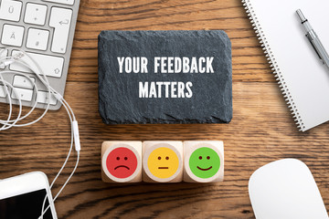 """cubes with a emoticons and slate plate with message """"your feedback matters"""" on wooden background"""