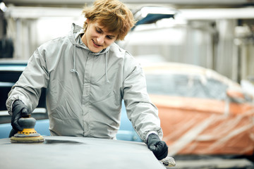 Auto mechanic grinds car part for painting. Car body work auto repair paint after accident