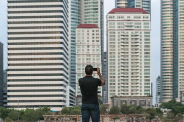 Man holding a smart phone and taking a picture with buildings in the city in background