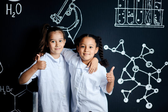 Two girls in white clothes, little future scientists, looking at camera while visiting school labaratory, standing with thumbs up against black board with sketches. Early development of children.