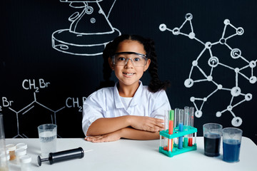 A little asian cute smiling girl wearing a doctor uniform and protective glasses looking at camera, future scientists sitting with folded hands in the laboratory. Educational concept.