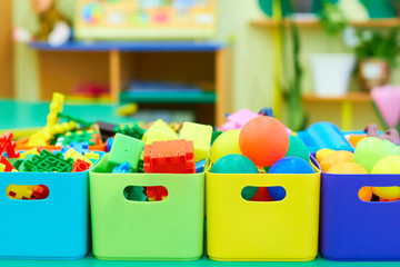 Toys in colored boxes. Cleanliness in the children's room.