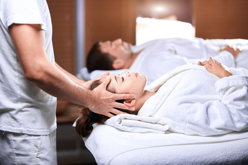 wellness, beauty, spa and relaxation concept - beautiful caucasian woman with closed eyes in spa salon getting head massage.