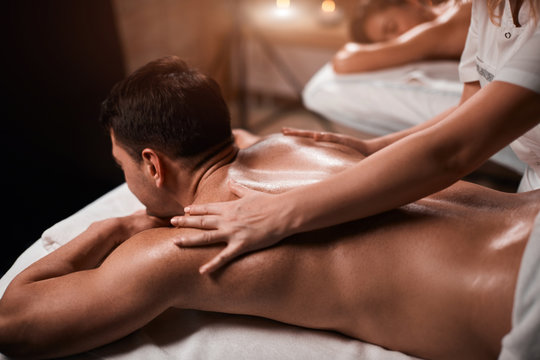 Handsome caucasian businessman and his beautiful wife treating themselves to a comforting back massage, a gentle relaxing massage at spa clinic.