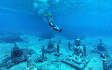 Young man snorkeling in the underwater Buddha temple