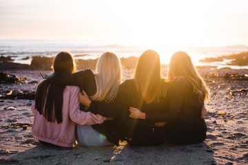 Rear view girls sitting on the beach and watching sunset