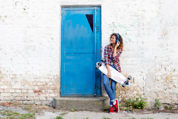 Girl with long skateboard standing and listening music