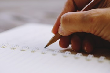 Close up of a man's hand writing in a notebook with pencil