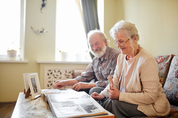 Sentimental memories. Senior Couple sitting at home on vintage sofa going through old photo albums, thinking about past days.
