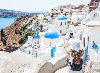 Woman taking photo with a smartphone in Greek Island